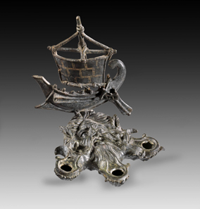Lot 234: Oceanus-shaped bronze lamp with attachment in the shape of a ship. Roman, 1st-2nd cent. AD. Lamp in the shape of bearded Oceanus' head with crab claws. At the head attachment in the shape of a Roman galley. From the Shlomo Moussaieff Collection, since 1948, Israel. With export permission from the Israel Antiquities Authority. Black-green patina, mast and edge of sail broken, mast repaired with a pin, tip of mast missing, parts of ropes missing, small hole on one nozzle. Estimate: 50,000,- euros. Hammer price: 55,000 euros.