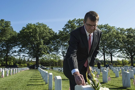 In May 2015, former Secretary of Defense Ashton Carter put a challenge coin on the headstone of a family friend. Photo: Department of Defense, Sean Hurt.