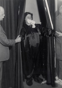 Helen Duncan emerging from curtains with 'ectoplasm' – her hands holding those of others at the séance. Edinburgh, 1933. Photograph © Senate House Library, University of London.